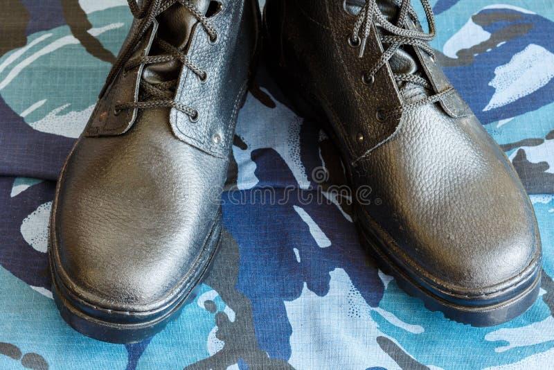 Bottes d'armée et ceinture d'armée sur le tissu bleu de camouflage De façon générale pour le soldat photos libres de droits