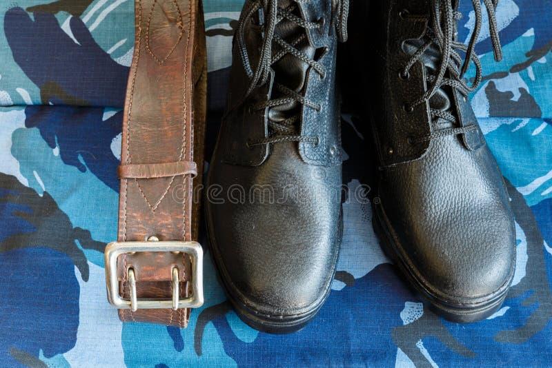 Bottes d'armée et ceinture d'armée sur le tissu bleu de camouflage De façon générale pour le soldat images stock