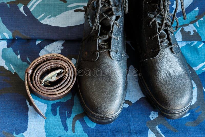 Bottes d'armée et ceinture d'armée sur le tissu bleu de camouflage De façon générale pour le soldat photographie stock