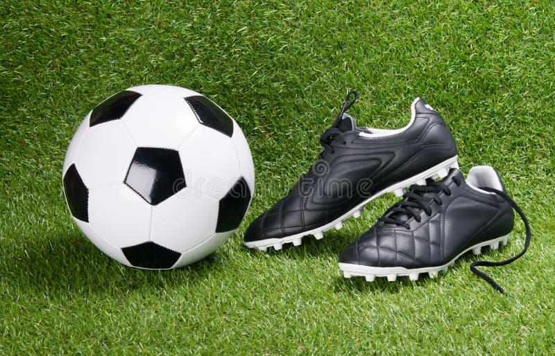 Bottes de ballon de football et de noir, dans la perspective d'herbe image stock