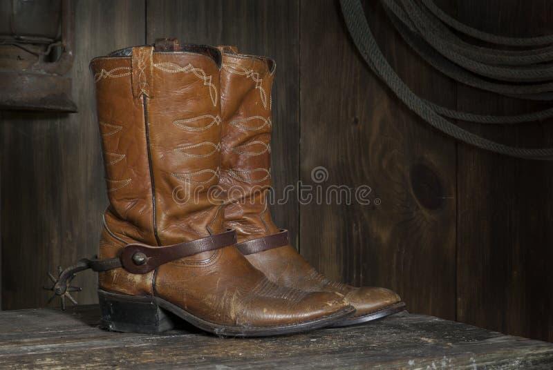 Bottes de cowboy dans la grange images stock
