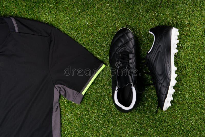 Bottes du football et une chemise de sports dans la perspective d'herbe images stock
