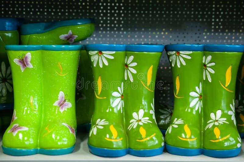 bottes en caoutchouc en céramique sur l'étagère dans le magasin photo libre de droits