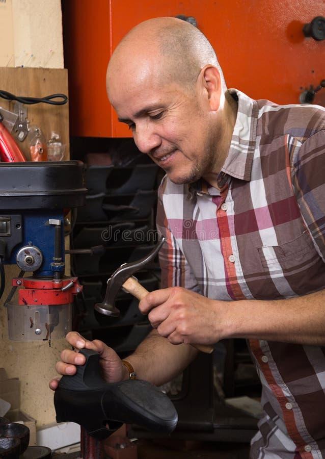 Bottes en cuir de couture d'ouvrier ordinaire sur le tour de point dans le worksho photos libres de droits