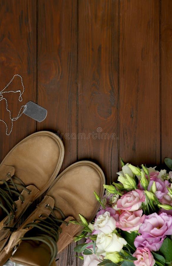Bottes et fleurs militaires sur la surface en bois, l'espace pour le texte Forces arm?es photos stock