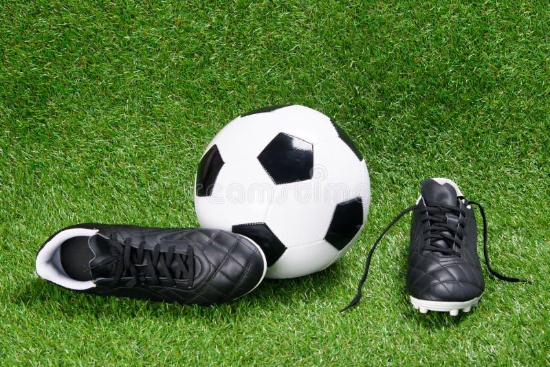 Bottes et une boule du football dans la perspective d'herbe photos stock