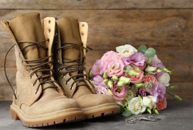 Bottes militaires avec des fleurs sur la surface grise, l'espace pour le texte Jour de forces arm?es photographie stock libre de droits