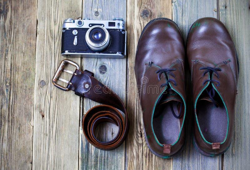 Bottes vigoureuses, ceinture en cuir, et caméra de télémètre - journaliste réglé photographie stock libre de droits