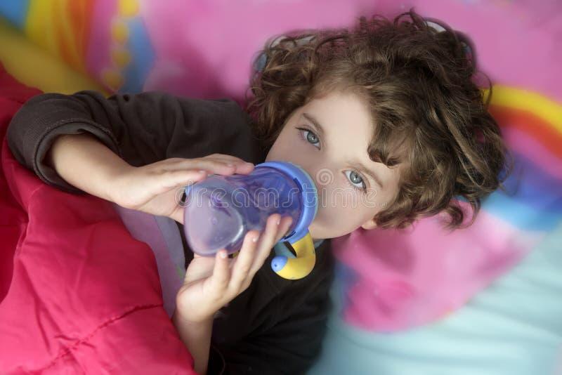 Bottiglia bevente della bambina adorabile immagine stock