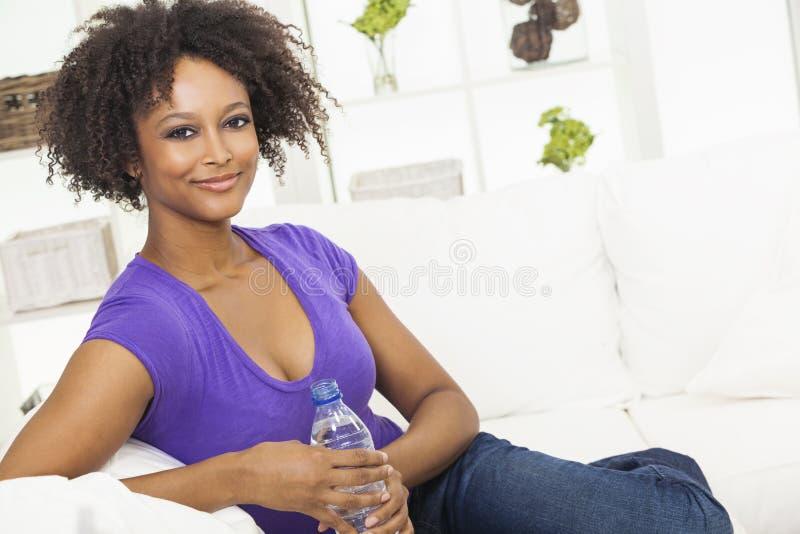 Bottiglia bevente della donna dell'afroamericano di acqua fotografia stock