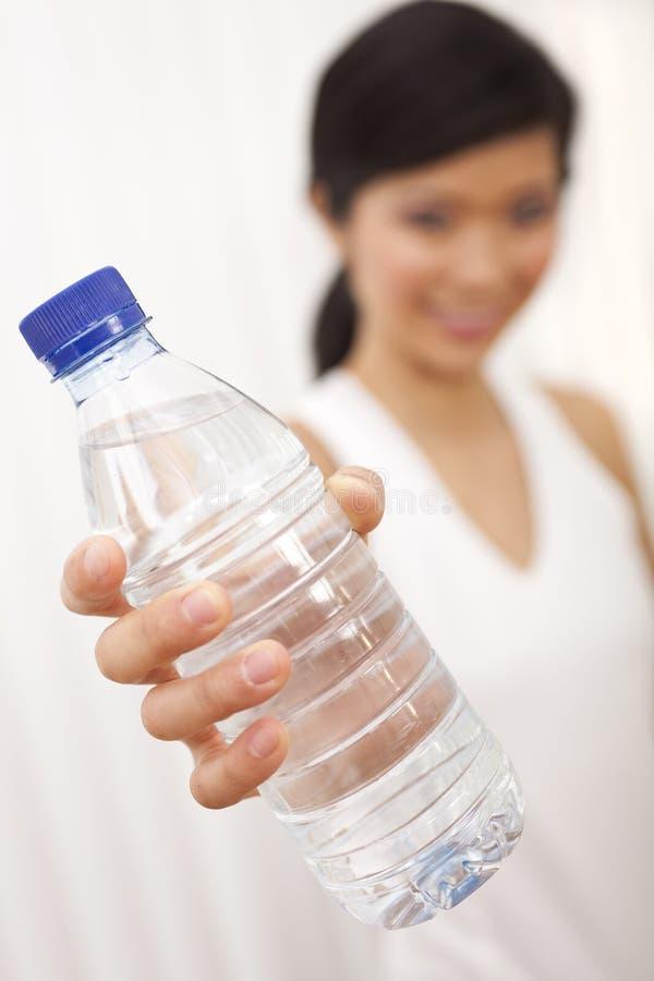 Bottiglia cinese asiatica della holding della ragazza di acqua pura fotografia stock