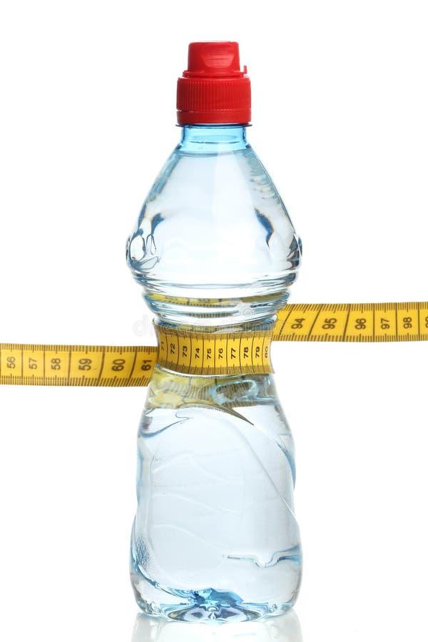 Bottiglia con acqua e nastro adesivo di misurazione fotografie stock