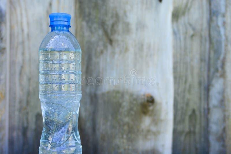 Bottiglia con acqua pulita fresca sul fondo di legno vago della parete fotografie stock libere da diritti