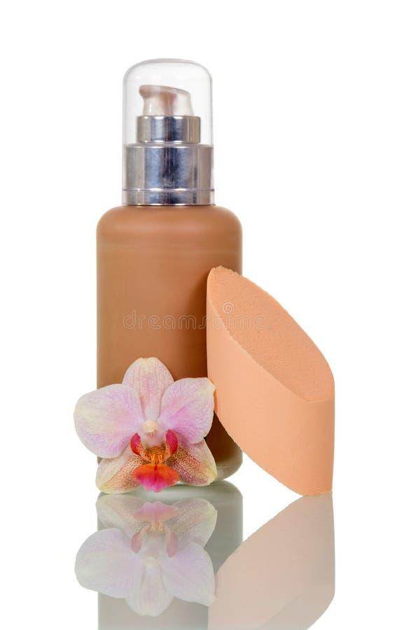Bottiglia con il correttore, spugna per l'applicazione, fiore dell'orchidea isolato su bianco fotografia stock