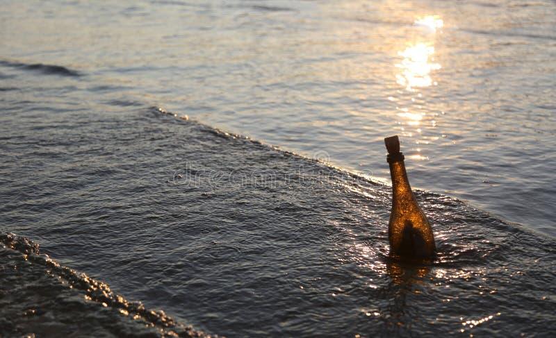 Bottiglia con il messaggio al tramonto fotografie stock
