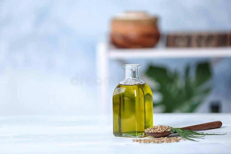 Bottiglia con il petrolio di canapa, i semi e le foglie fresche immagini stock libere da diritti