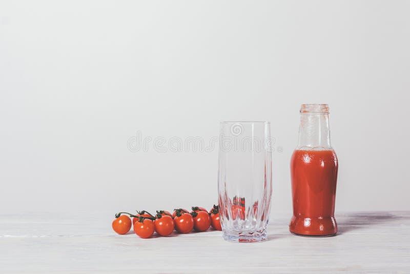 Bottiglia con il succo di pomodoro e un vetro fotografia stock libera da diritti