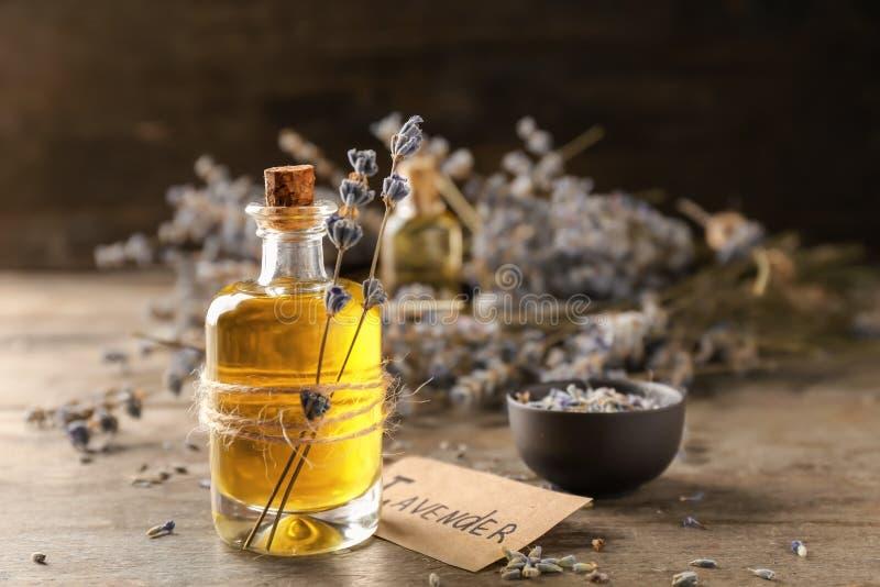 Bottiglia con l'olio essenziale della lavanda sulla tavola di legno fotografia stock libera da diritti