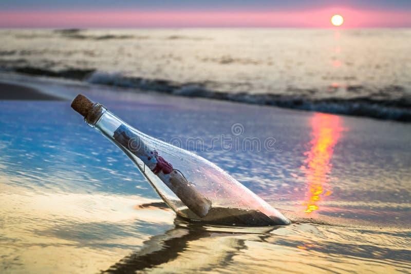 Bottiglia con un messaggio gettato dal mare fotografie stock libere da diritti