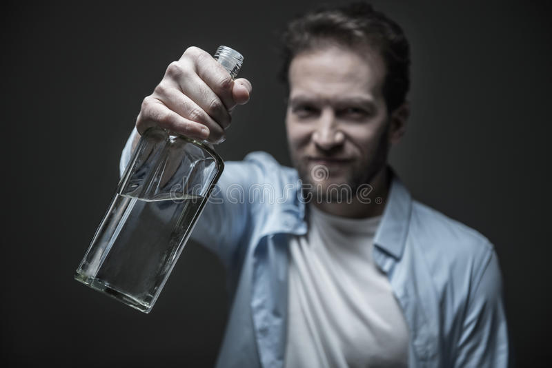Bottiglia contentissima positiva della tenuta dell'uomo con alcool immagini stock libere da diritti