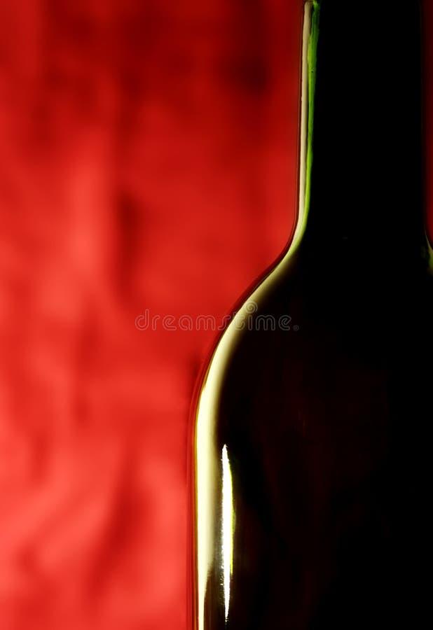 Bottiglia contro una priorità bassa rossa immagine stock libera da diritti