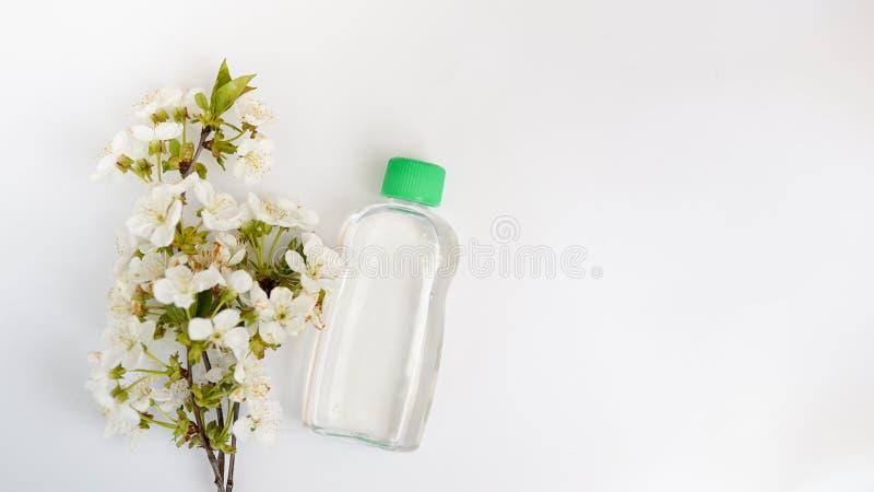 Bottiglia cosmetica con i fiori isolati su fondo bianco acqua o toner con olio essenziale, la vista superiore, la derisione marca immagine stock libera da diritti