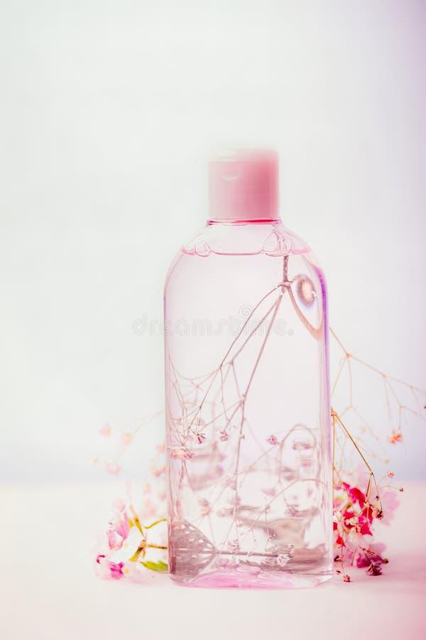 Bottiglia cosmetica del prodotto con acqua o tonico micellare per cura di pelle, fiori rosa, colore pastello, vista frontale immagine stock