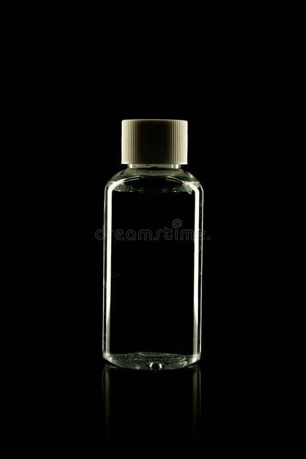 Bottiglia cosmetica del prodotto per crema, schiuma, sciampo su fondo nero fotografia stock