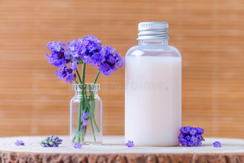 Bottiglia cosmetica naturale con i fiori freschi della lavanda fotografie stock libere da diritti