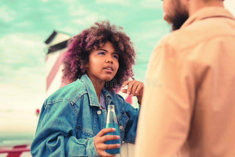Bottiglia curiosa della tenuta della ragazza ed ascoltare attentamente il giovane fotografia stock