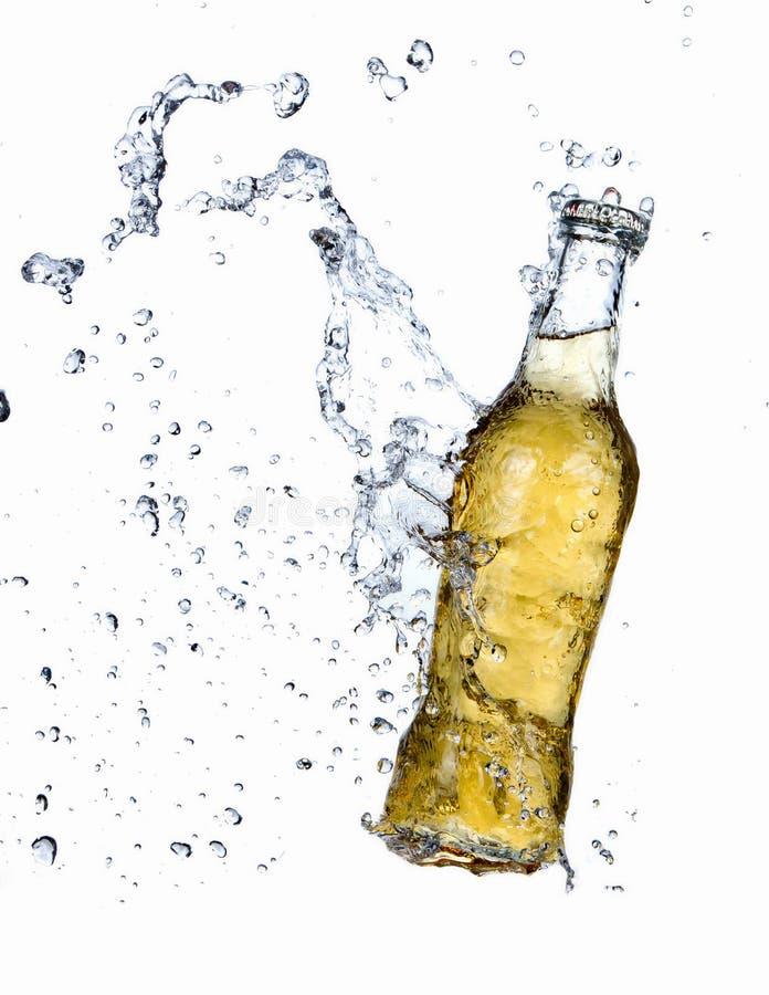 Bottiglia da birra con acqua che spruzza dalla bottiglia fotografie stock libere da diritti
