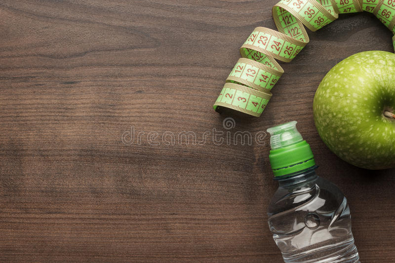 Bottiglia del nastro di misurazione dell'acqua e del verde fresco immagine stock libera da diritti