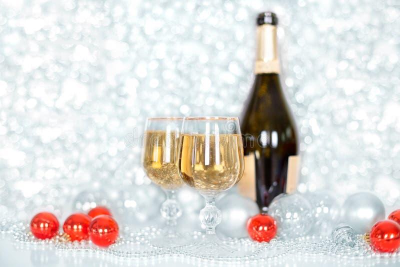 Bottiglia del nuovo anno o di Natale di champagne, due vetri pieni di champagne sulle palle brillanti e scintillare della tavola, fotografia stock