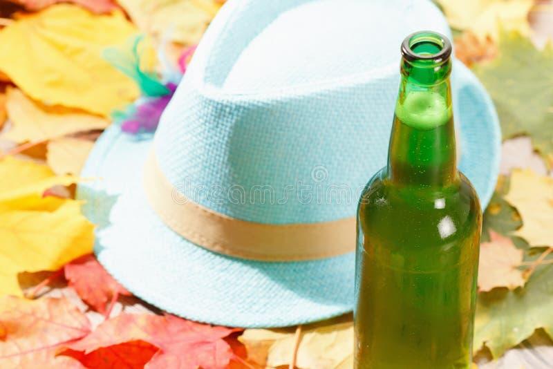 Bottiglia del picnic più octoberfest della pinta di vetro di birra su sfondo naturale con il cappello e le foglie di autunno immagini stock