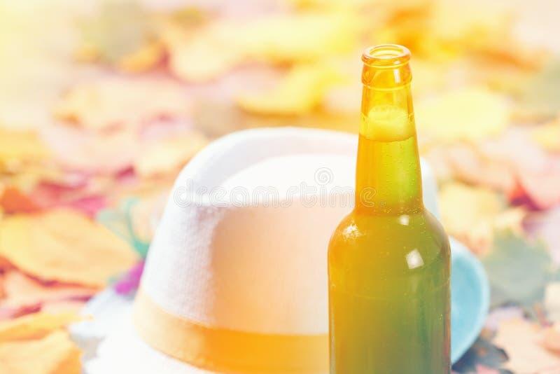 Bottiglia del picnic più octoberfest della pinta di vetro di birra su sfondo naturale con il cappello e le foglie di autunno fotografie stock libere da diritti