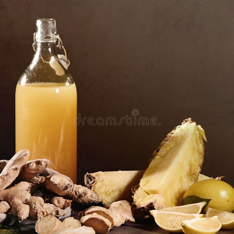 Bottiglia del succo di ananas casalingo con lo zenzero, il limone e gli ingredienti fotografia stock libera da diritti
