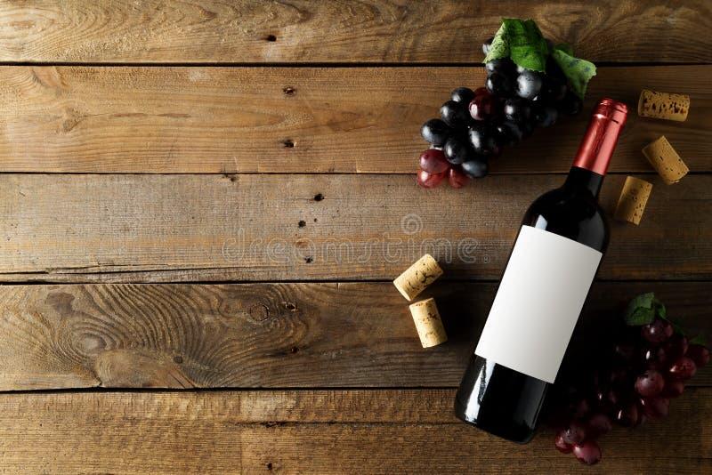 Bottiglia del vino rosso con l'uva ed i sugheri sulla tavola di legno rustica marrone posta pianamente da sopra fotografia stock libera da diritti