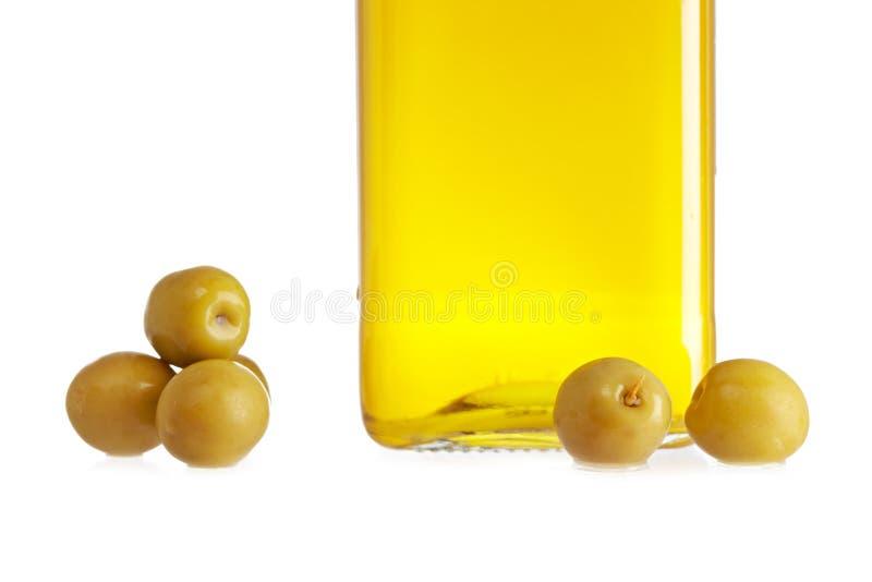 Bottiglia dell'olio di oliva e determinate olive fotografia stock