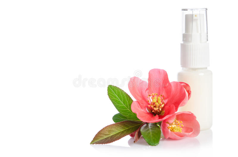 Bottiglia della crema di fronte con il fiore rosa immagini stock libere da diritti