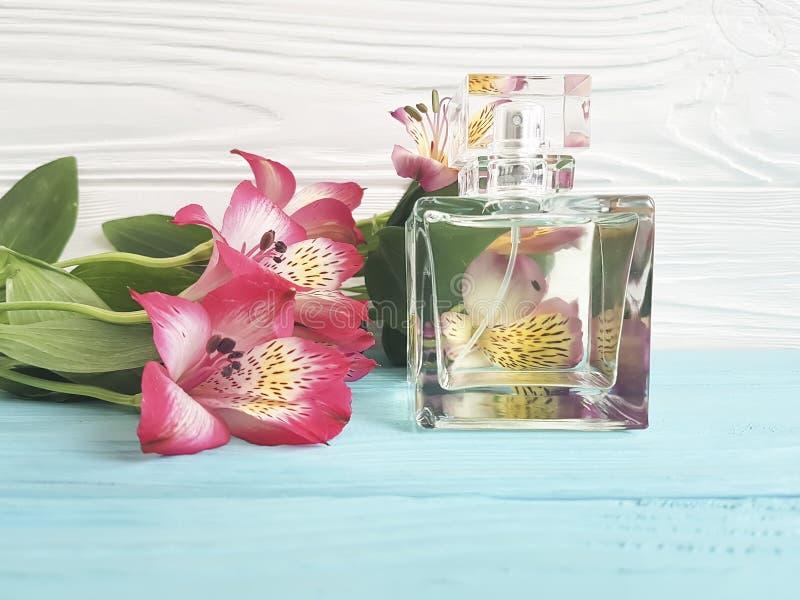 Bottiglia della decorazione di alstroemeria del fiore del profumo bella su un fondo di legno fotografia stock libera da diritti