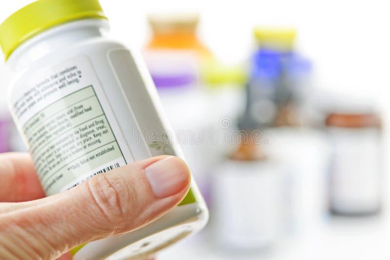 Bottiglia della medicina della holding della mano immagini stock libere da diritti