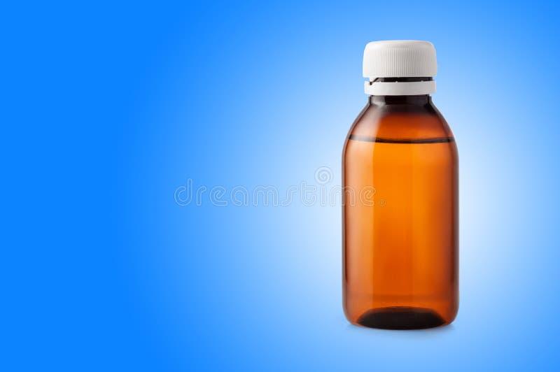 Bottiglia della medicina di plastica marrone su fondo blu immagine stock