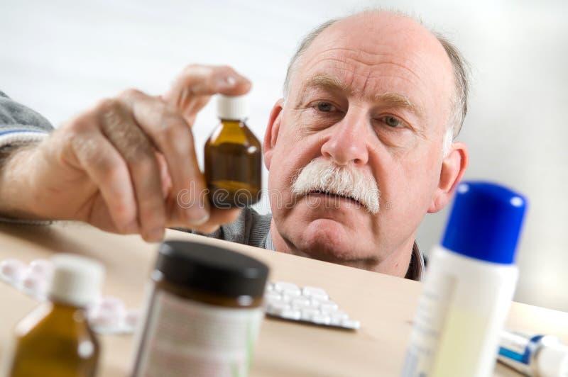 Bottiglia della medicina di raccolto dell'uomo maggiore immagini stock