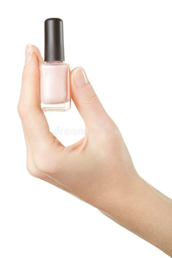 Bottiglia dello smalto della tenuta della mano della donna fotografie stock libere da diritti