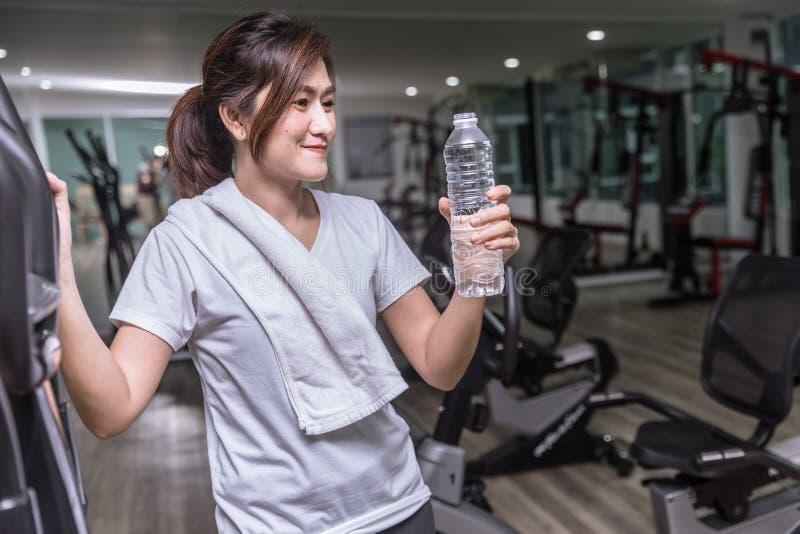 Bottiglia di acqua bevente della ragazza della tenuta asiatica della mano nel club di sport fotografia stock libera da diritti