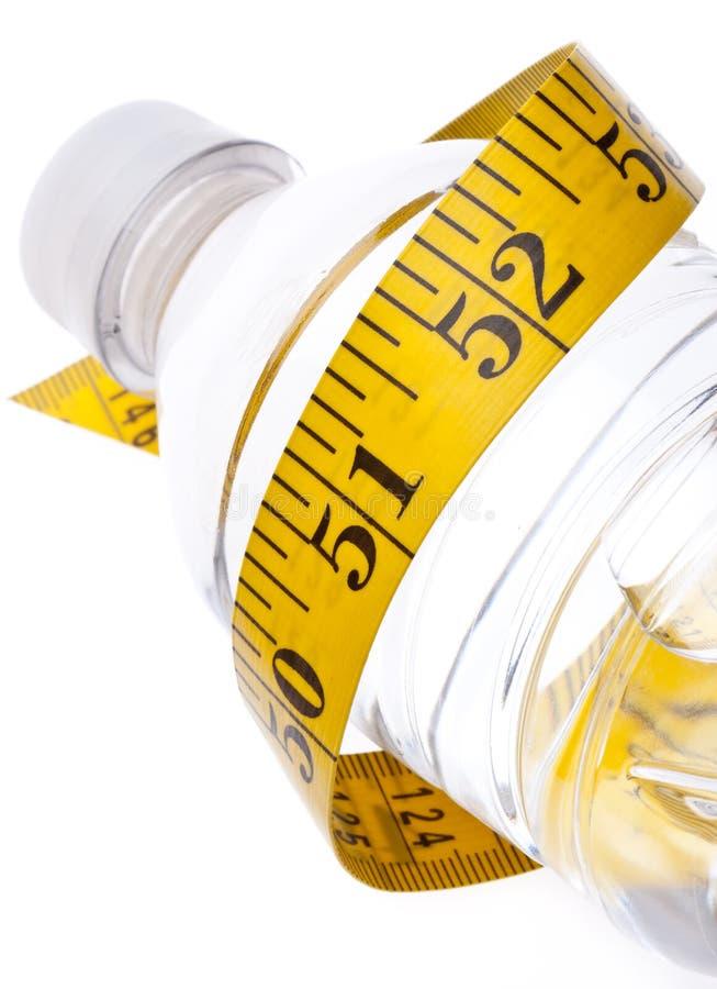 Bottiglia di acqua con lo stile di vita sano di misurazione del nastro fotografia stock