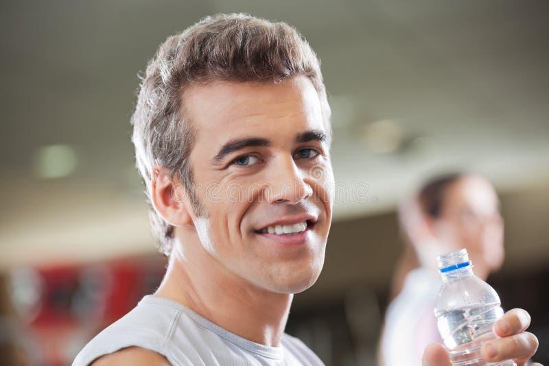 Bottiglia di acqua della tenuta dell'uomo nel club di salute immagine stock