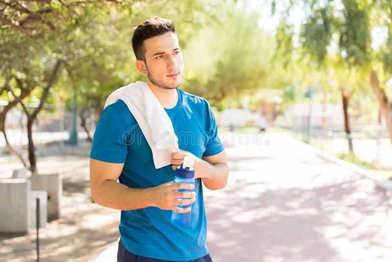 Bottiglia di acqua maschio premurosa della tenuta dopo l'esercizio in parco fotografie stock