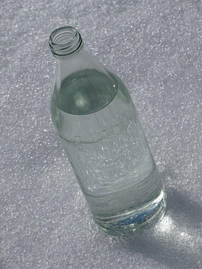 Bottiglia di acqua nella neve immagini stock libere da diritti