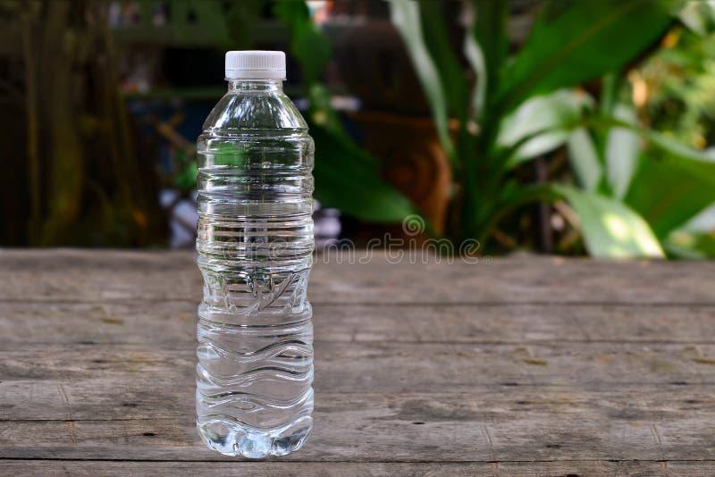 Bottiglia di acqua sulla vecchia tavola di legno nel giardino immagine stock libera da diritti